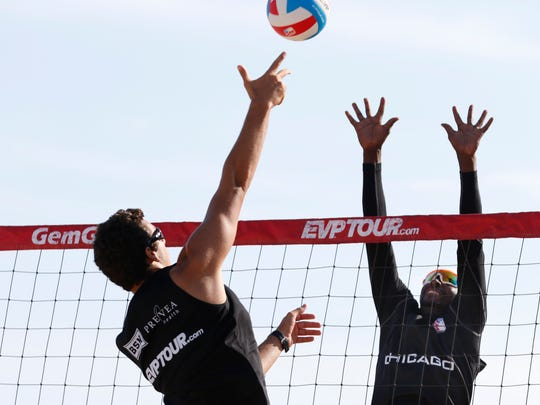 Sage Newgard, left, spikes the ball while Easy Liese tries to block it during the EVP® Beach Volleyball Tour's Coolest Coast Pro Am men's championship game on Neshotah Beach on Saturday, July 16 in Two Rivers.  Newgard and his partner, Jiri Kapalek won the championship title after winning two sets in a row.