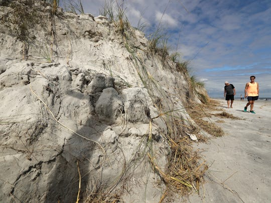 People look at a cliff formed by erosion from Hurricane Matthew on the beach at Jacksonville Beach, Fla. Saturday, Oct. 8, 2016. The fast-weakening storm continued its march along the Atlantic coast Saturday.