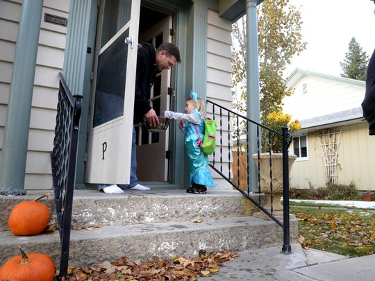 Mirabelle Heiser, age 2, picks out candy from Rick Podry. Don't feel like going door to door? There are plenty of other Halloween options around Great Falls.