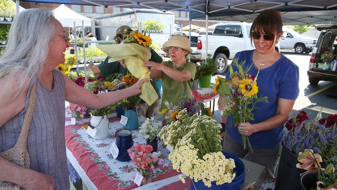 Lee Caine of Brighton purchases an arrangement of freshly picked flowers from Dana Dore-Hadad, at her Chicory Blue Gardens of Spencerport stand at the Brighton Farmer's Market Sunday, June 26, 2016 in the parking lot of Brighton High School.  At right, assistant Emily Davis works on another arrangement.