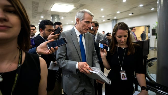 Sen. Rob Portman talks with reporters in the basement of the U.S. Capitol.