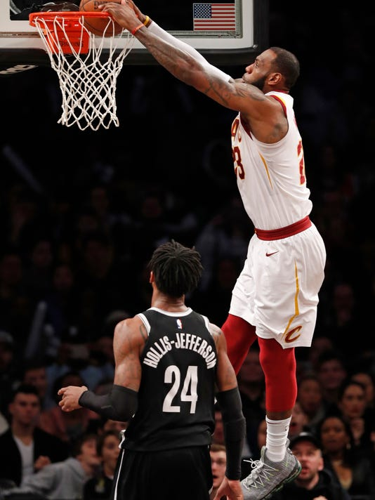 Cleveland Cavaliers forward LeBron James (23) dunks over Brooklyn Nets forward Rondae Hollis-Jefferson (24) during the second half of an NBA basketball game, Sunday, March 25, 2018, in New York.The Cavaliers defeated the Nets 121-114. (AP Photo/Kathy Willens)