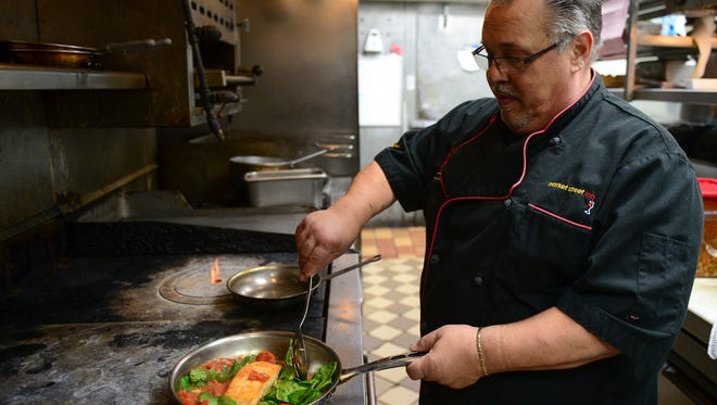 Vinny Bellia prepares his grilled salmon over hot spinach salad that will be a feature item on the menu at Market Street Inn on Tuesday nights featuring select items from his previous restaurant vinny's la roma.
