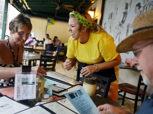Twila Rupp, of North Codorus Township, moves the umbrella in her cocktail as she and her husband, John, prepare to order from server Courtney Golden during the second Summer Beach Party Weekend at Mudhook Brewing Co. on Friday, June 13, 2014. The event returns on Friday and Saturday for the third year. It features 12 tons of sand, as well as live music on both days.