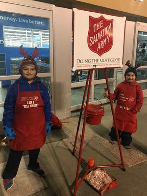 Derek and Nikolas Peters, students at the Bailey Park and Davis Elementary Schools, mans the kettle at Wal-Mart during the Christmas season.