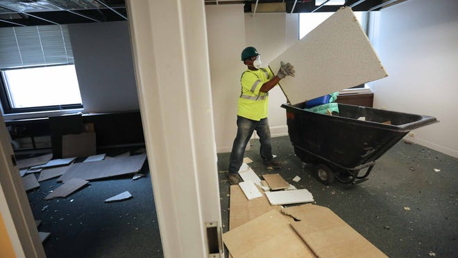 A construction worker removes old ceiling tiles from an office at Chemours in the DuPont Building.