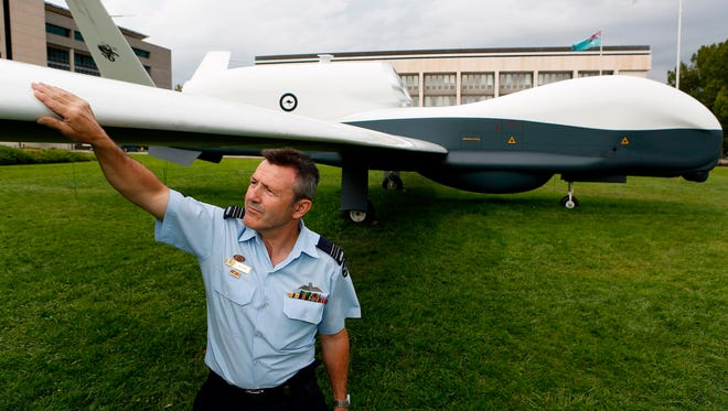 This handout photo taken on April 3, 2014 and received from the Australian Department of Defence on June 26, 2018, shows Squadron Leader Col Gray inspecting a full scale mock up of the MQ-4C Triton Unmanned Aerial Vehicle in Canberra.