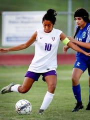 Smyrna's Ashley Barrientos kicks upfield during a 2018 match against La Vergne. Lady Wolverine Annette Mateos (17) defends.
