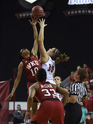 USD's Margaret McCloud (30) and Western Kentucky's Tashia Brown (10) reach for the ball at tipoff Sunday at the WNIT quarterfinal at the DakotaDome, March 27, 2016.