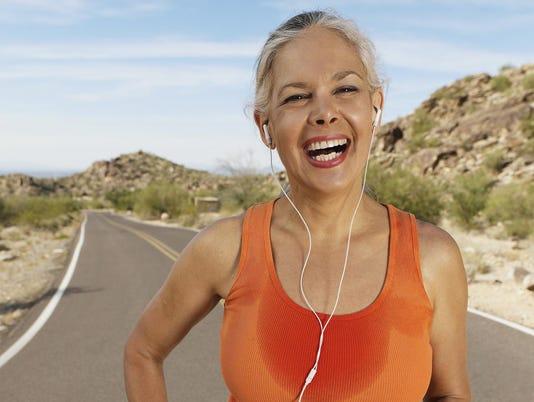 Sweaty senior Hispanic woman listening to ear buds