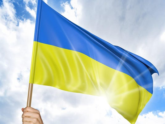 Person's hand holding the Ukrainian national flag and waving it