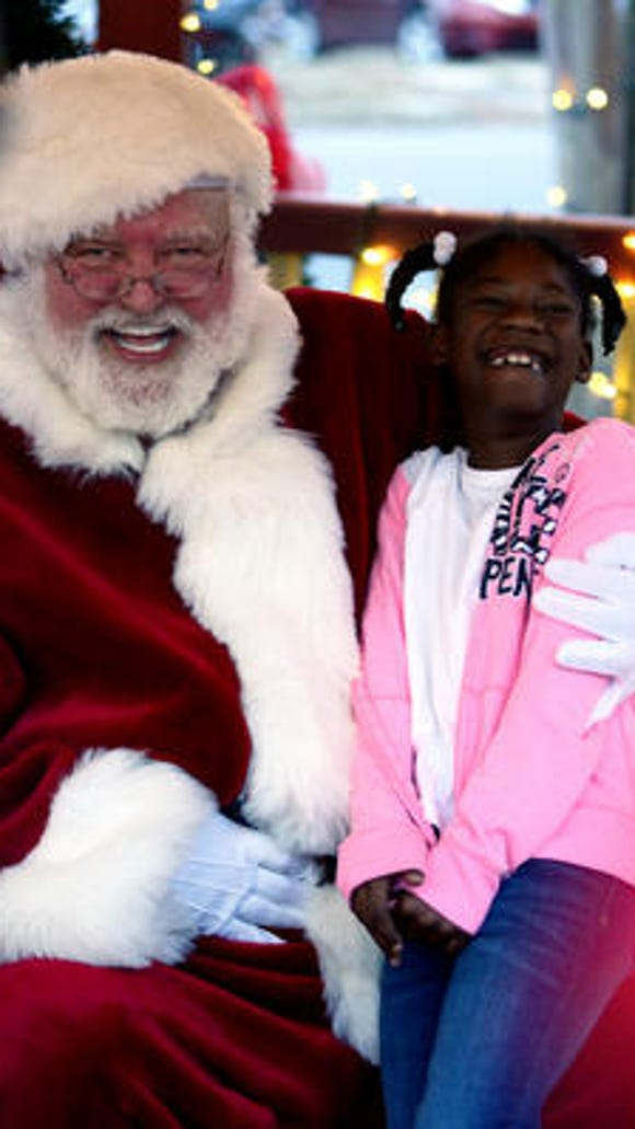 Zyrea Brown, 8, laughs with Santa Claus at the City of Hattiesburg's Christmas tree lighting ceremony at Town Square Park Thursday.