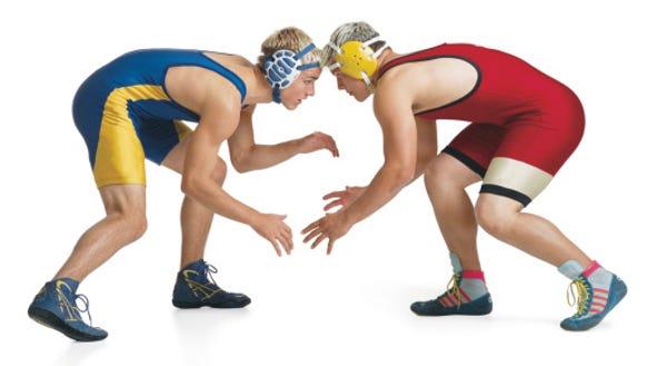 two teenage caucasian male wrestlers from opposing