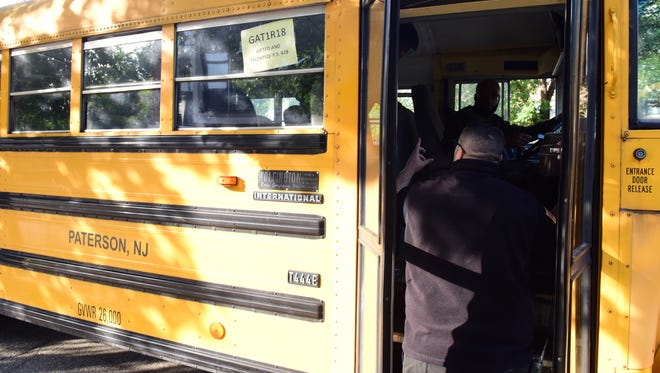 Ledio Llupa, a Paterson public school officer, makes sure each bus is empty before it leaves School 28 on Tuesday. A new policy has been put in place to ensure that no children are left behind on buses.