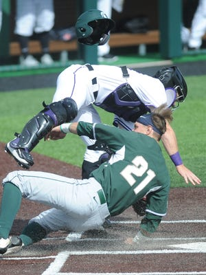 Michigan State runner Dan Chmielewski (21) upends ACU catcher Cole Solomon while scoring on Kory Young's sacrifice fly in the second inning. The Spartans won the opener of the doubleheader 9-7 and won the second game 19-7 on Saturday, Feb. 18, 2017 at Crutcher Scott Field.