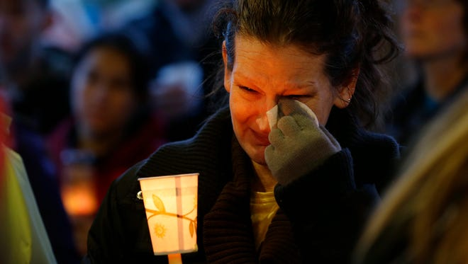 Teresa Welter cries as she holds a candle March 25  at a vigil in Arlington, Wash., for the victims of a massive mudslide.