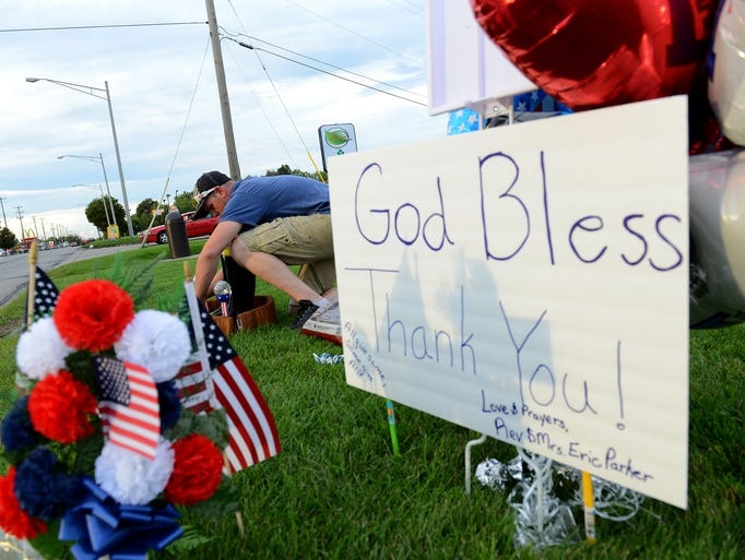 Andy Porter, of Lansing, works on a memorial tribute