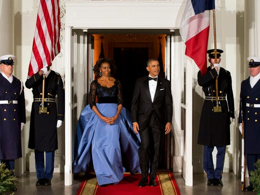 First lady Michelle Obama and President Obama wait for the arrival of French President Francois Hollande for a state dinner.