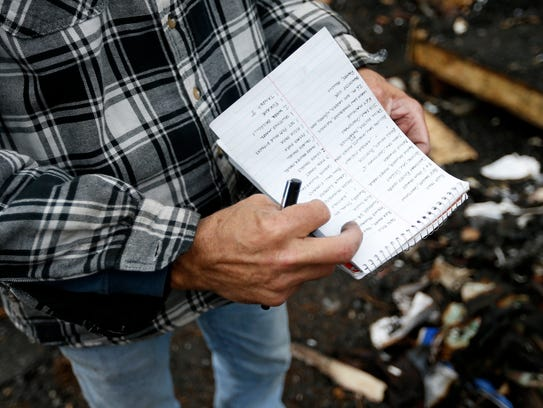 Alan Edes takes inventory of items destroyed in a shed