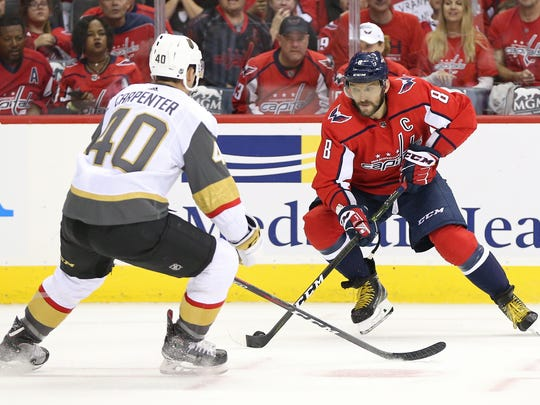 Washington Capitals left wing Alex Ovechkin, right, skates with the puck as Vegas Golden Knights center Ryan Carpenter defends during the first period in Washington, Oct. 10, 2018.