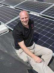 Terry Dvorak poses with the solar panels his Norwalk-based company Red Lion Renewables installed on the roof of the St. John the Apostle Catholic Church in Norwalk. Dvorak is a parishioner at the church.