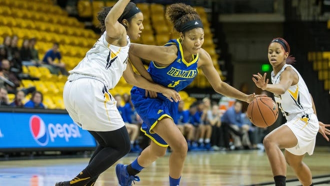 Delaware's Makeda Nicholas muscles her way to the basket as Towson defenders close in.