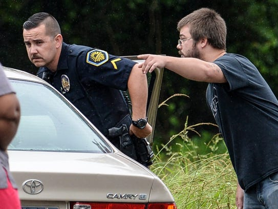 An Anderson police officer listens to a man pointing