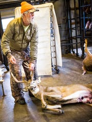Merv Mitzel, Jr., of Red Lion, drags a buck he shot on a farm, into Miller's Meats on the first day of rifle season for deer.
