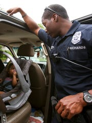 Indianapolis Metropolitan Police Department officer Javed Richards looks after a young girl as other officers speak with her mother,  Downtown Indianapolis on June 3, 2016.