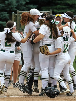 Howell softball players celebrate their 3-2 victory over Plymouth in the state Division 1 quarterfinals at Chelsea on Tuesday, June 12, 2018.