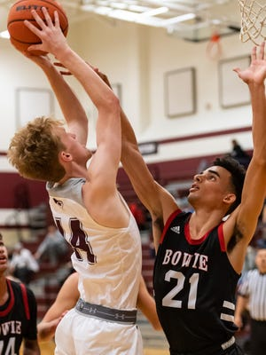 Andrew O'Neal, left, takes a shot for Round Rock against Cade Holzman. Round Rock won a nondistrict boys basketball game at home over Bowie 64-50 on Monday.