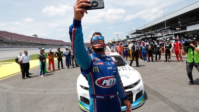 Driver Bubba Wallace takes a selfie with himself and other drivers that pushed his car to the front in the pits of the Talladega Superspeedway prior to the start of the NASCAR Cup Series auto race at the Talladega Superspeedway in Talladega Ala., Monday June 22, 2020. In an extraordinary act of solidarity with NASCAR's only Black driver, dozens of drivers pushed the car belonging to Bubba Wallace to the front of the field before Monday's race as FBI agents nearby tried to find out who left a noose in his garage stall over the weekend.