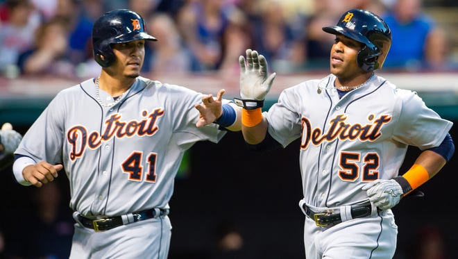 Tigers DH Victor Martinez and leftfielder Yoenis Cespedes celebrate after scoring on a double by third baseman Nick Castellanos during the fifth inning of the Tigers' win Tuesday in Cleveland.