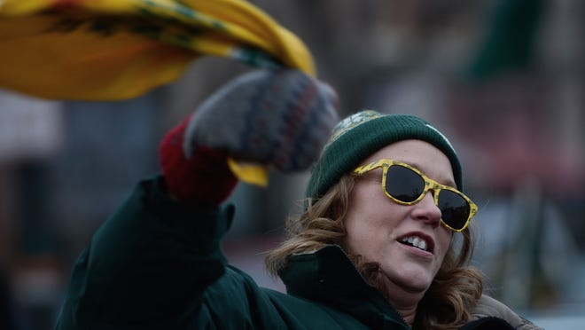 Green Bay resident Carri Prigge waves a towel during a rally for the Packers in downtown Green Bay at the Packers Heritage Trail on Friday.