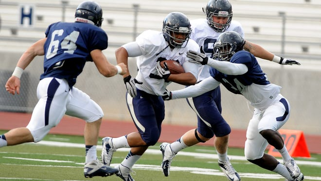 Travis Wilson, right, makes a tackle during a 2013 scrimmage. He's expected to make his first career start in Nevada's season opener Friday.