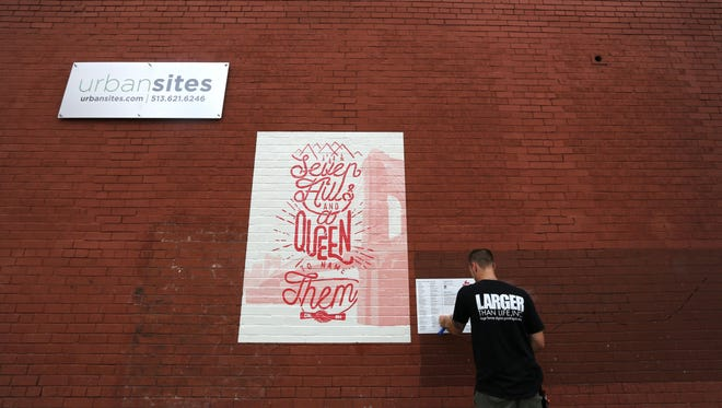 Kevin Scott, of Larger than Life digital printing, installs signage for the mini-mural by Powerhouse Factories.