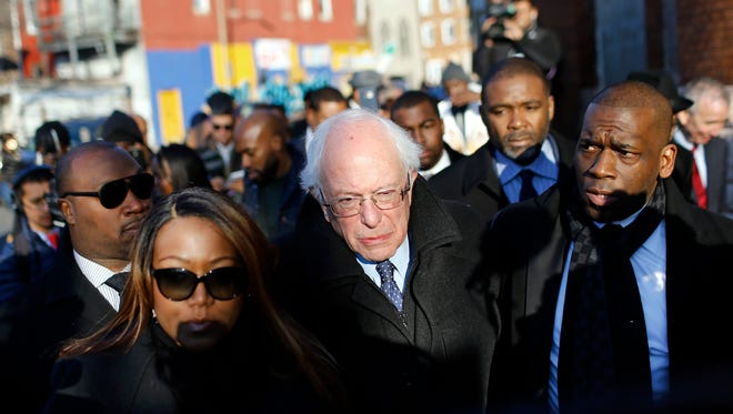 Democratic presidential candidate, Sen. Bernie Sanders, I-Vt., center, walks alongside the Rev. Jamal Bryant, right, during a walking tour of the Sandtown-Winchester neighborhood of Baltimore, Tuesday, Dec. 8, 2015. The Democratic candidate was touring the neighborhood of Freddie Gray, who died last spring of a spinal injury he suffered while in police custody, touching off riots.
