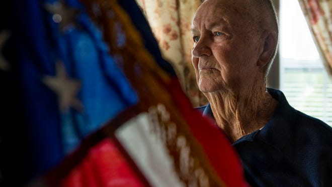 Samuel Corey, 86, a retired command sergeant major, poses for a portrait behind an American flag in his home.
