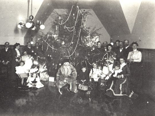 The Christmas gift-giving in the attic of the home, with Santa Claus in the front, around 1890.