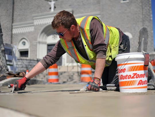 Concrete finisher Francis Phillips works on a Landis