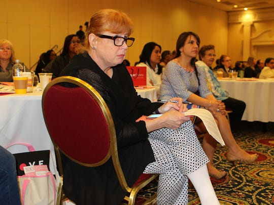 An attendee of the 20th Annual Breast Cancer Update takes notes during a panel discusiion on Tuesday in Dover.