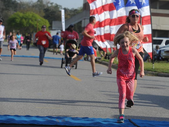 Runners make their way to the finish line Saturday morning during the Blue Angels Rock N Fly Half Marathon and 5k at Naval Air Station Pensacola.