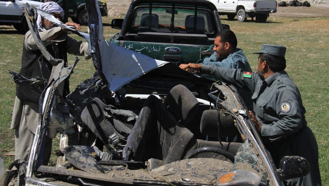 Afghan security personnel inspect the site of a roadside bomb explosion in Behsood district of Jalalabad east of Kabul, Afghanistan, Wednesday, April, 22, 2015. In eastern Nagharhar province, where the Taliban have long been active, Ahamd Zia Abdulazai, spokesman for the provincial governor, said that a prosecutor and his driver were killed when their vehicle hit a roadside bomb in Behsud district.