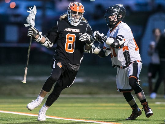 Central York's Garrison Markey (8), tries to shake York Suburban defender Phinean Smith (31), during the first  quarter of a boys' lacrosse match Thursday, March 30, 2017, at York Suburban High School in Spring Garden Township. Central York won 9-7. Amanda J. Cain photo