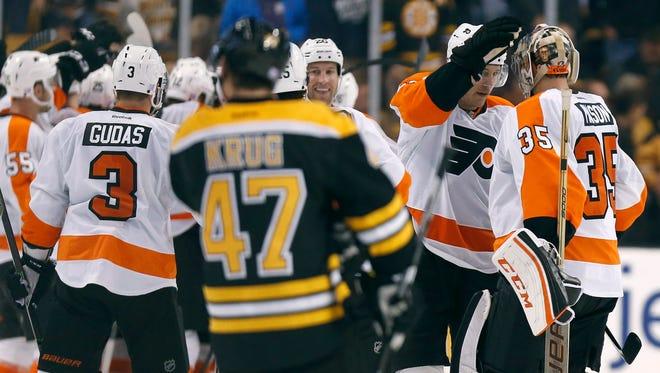 The Philadelphia Flyers celebrate with goalie Steve Mason (35) in front of Boston Bruins' Torey Krug (47).