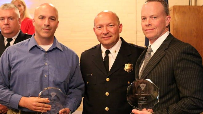 Police Chief Ken Miller stands with the two men credited for helping a woman escape a carjacking suspect.