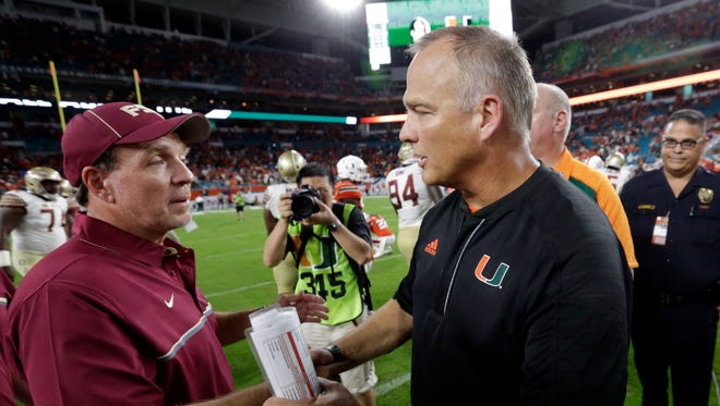 Miami head coach Mark Richt, right and Florida State head coach Jimbo Fisher, meet at the end of a NCAA college football game, Sunday, Oct. 9, 2016, in Miami Gardens. Florida State defeated Miami 20-19. (AP Photo/Wilfredo Lee)