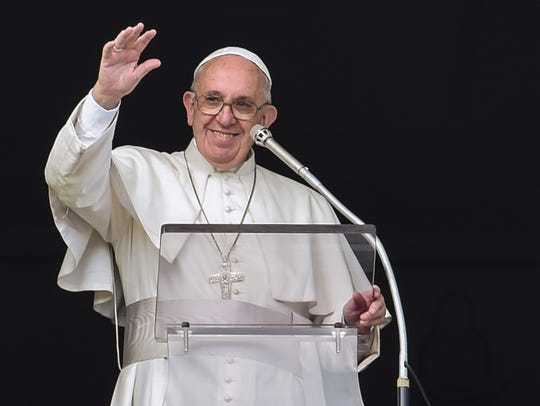 Pope Francis waves to the crowd from the window of
