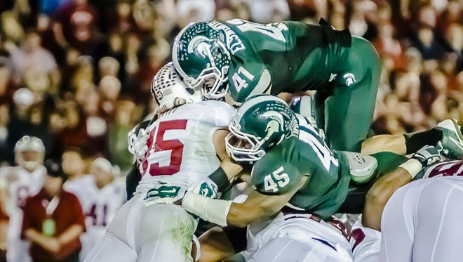 Kyler Elsworth (41) and Darien Harris (45) stop Ryan Hewitt of Stanford on fourth-and-1 with 1:45 left in the 2014 Rose Bowl.