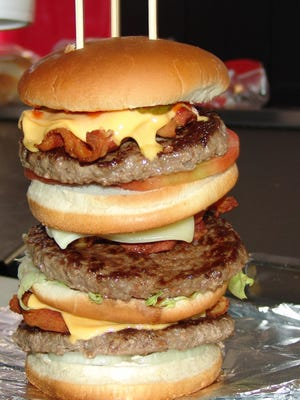 The Monster Burger at The Freeze is so tall it has to be held together with skewers. It weighs more than 2 pounds and has three 8 ounce chop sirloin patties, nine slices of bacon, American and Swiss cheese.